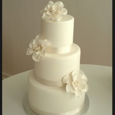 i like the flowers, except on a square cake with feathers behind them. pearls around each layer.