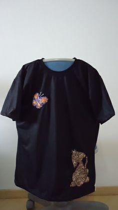 Cor preta, tamanho M, malha de excelente qualidade, decote redondo, com apliques de gatinho e borboleta.  Aplico esse desenho em camisetas de outra cor e tamanho, porém, as cores e estampas dos tecidos podem variar de acordo com a disponibilidade e com a cor da camiseta escolhida. R$ 35,00