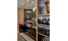 O designer de interiores João Feire foi o responsável por projetar o ambiente Sala de jantar do executivo, de 33m². O mobiliário clean e, ao mesmo tempo, imponente, foi a opção do profissional para criar um espaço com requinte e sofisticação. Tons e texturas foram utilizados para representar um ambiente masculino. Além disso, o mix de texturas da laca preta com a madeira concedeu equilíbrio para o espaço. O destaque fica por conta da parede ornada com espelhos e a estante.