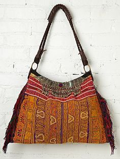 Vintage Necklace Hobo | Hand embroidered hobo back with colorful yarn fringe trimming on each side. Top of front is trimmed with vintage metal necklaces with glass detailing and metal fringe embellishment. Top of bag zips close.  Woven leather handle. Inside is fully lined with one zipper pocket.   *By JADETribe