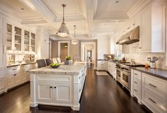 """Perimeter countertop is Polished Quartz. Color: Stormy Sky. Wall: Benjamin Moore Shale. Cabinets: White Dove Hardware is the Emtek Geometrical Cabinet Pull. Island countertop is White Arabesque Honed Marble.Faucet is the """"Quincy Pull Down Faucet by Kallista""""."""