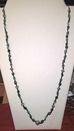 knotted leather with smooth emerald stones and silver beads.