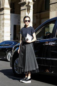 Inspiração street style look preto total com saia mídi, mocassim, t-shirt preta e cinto bold.