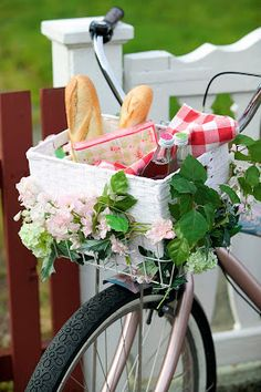 In the white basket on a bike, a picnic is ready with flowers surrounding the box