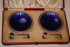 "Gustav Gaudernack for David Andersen.Two small gilt silver dishes with blue enamel. Guilloche  ground, gold inlay pattern and peripheral white enamel pattern. Two small ""tongs"" in same pattern. David andersen hallmarks and English sterling export marks."