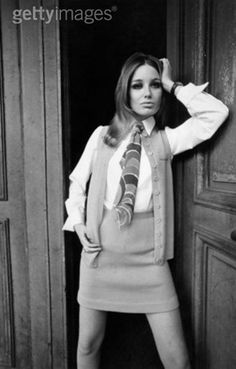 Jane Lumb models a knitted suit by designer Dorothy Bis, comprising an orange skirt and waistcoat, and a brightly coloured tie, 1967.