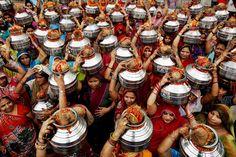 MUJERES lavadora: Mujeres que lavan ropa para ganarse la vida lleva a las ollas de agua y el coco, ya que realiza un ritual hindú en Nueva Delhi el lunes. (Rajesh Kumar Singh / Associated Press)