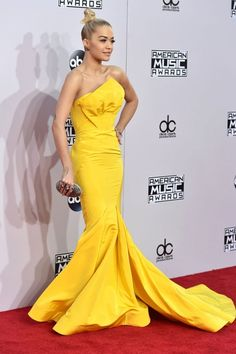 Rita Ora in a bright yellow Zac Posen gown with a long train at the 2014 AMAs.