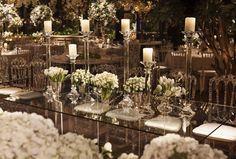 Glass table decorated with white flowers and  candles.