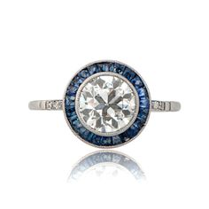 A gorgeous diamond and sapphire halo engagement ring, set in a delicate handmade platinum mounting and accented with diamonds along the shoulders.