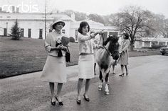 Jacqueline Kennedy takes Empress Farah (left) on a tour of the White House grounds. The Empress is the wife of the Shah of Iran. Mrs. Kennedy is leading Caroline's pony, Macaroni, who had tried to eat the flowers that Empress Farah was carrying.