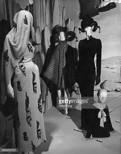 Schiaparelli | A display of French fashions at the preview of an exhibition of 20th Century fashion at the Victoria and Albert Museum, London 12th October 1971. The exhibition has been designed by Michael Haynes, with exhibits selected by photographer Cecil Beaton. At far left is a 1938 pale blue evening outfit with 'tear' motifs by Schiaparelli. At centre is a 1938 gold and silver evening cape, also by Schiaparelli. At second right is a 1938 French black evening dress with black 'top' hat…