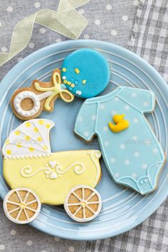 Baby shower cookies. Blue & Yellow baby stroller, onesies and rattle. Ideas for baby shower sugar cookies decoration. Stock photo.
