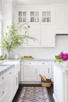 A pink and gray vintage rug sits in front of a farmhouse sink fixed to white shaker cabinets donning polished nickel pulls and a Super White Quartzite countertop.