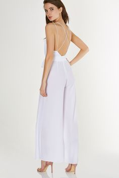 39ed06d947a9 Deep V-neck jumpsuit with strappy design. Wide leg fit with open slits on