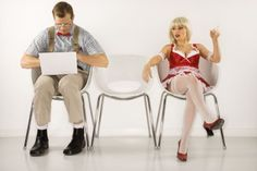 Caucasian young man dressed like nerd sitting with laptop with Caucasian young blonde woman looking at him.