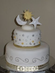 This cake is covered in marshmallow fondant.  The spirals and dots are piping gel with silver luster dust mixed in.  The sun, moon, and star decorations are marshmallow fondant painted with luster dust.