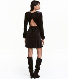 Sort. En kort kjole i velour med glans. Kjolen har omslag bak med utskåret parti i ryggen. Lange ermer med elastikk nederst. Avskåret i midjen med
