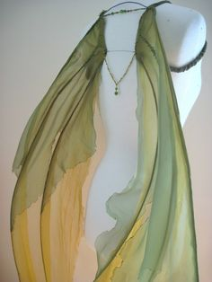 They are made from green polyester organza and amber orange rayon chiffon sewn over a heavy duty 12 gauge bailing wire frame. The edges of the fabric have been burnt and singed to give them that ethereal quality. Seed beads have been hand sewn along the veins and glass bead detail has been added to the back.  The tips of the wings are finished with coiled wire and green glass beads.   They comfortably attach around the arms with elastic. The wire frame is fully bendable and can be adjusted