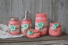 Rustic mason jar bathroom jar set. Hand painted in coral, lightly distressed, wrapped with white burlap, tied with jute and mint green roses, finished with a protective coating. Metal soap dispenser, toothbrush holder, make up brush holder, cotton swab jar, cotton ball jar, or many other uses!  Do not immerse in water, clean with a damp cloth. The jars range in height from 6.5 to 2 tall and 3.5 to 3 in diameter.  This set can be painted any color you like, or with any assortment of jar…