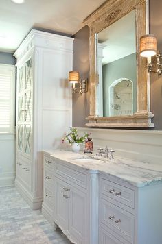 Bathroom Distressed Mirror. Flawless white master bathroom suite. Custom tall linen storage, rustic mirror, white inset cabinetry, and marble countertop. #bathroom #reclaimedwoodmirror #Bathroommirror bathroom-distressed-mirror