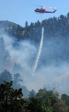 A helicopter drops water on the Waldo Canyon Fire along U.S. Highway 24 west between the Waldo Canyon Trailhead and Cascade, Colo., Tuesday, June 26, 2012. Colorado has endured nearly a week of 100-plus-degree days and low humidity, sapping moisture from timber and grass, creating a devastating formula for volatile wildfires across the state and punishing conditions for firefighters.