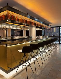The brass-clad bar transforms from a spot for coffee and pastries in the morning to a bustling destination for cocktails in the evening. A floating shelf lined with liquor bottles in amber hues gives the area a warm glow.