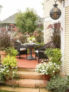 Pic only...Cheap And Easy Landscaping Ideas - love the lanterns and planters with purple fountain grass and sweet potato vines