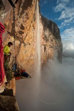 Waterfall mist and parting clouds from the jungle canopy greet Patagonia climbing ambassador Sean Villanueva at sunrise, midway up the new route, Maria Rosa. Amuri Tepui, Venuzuela. Photo: Jean-Louis Wertz