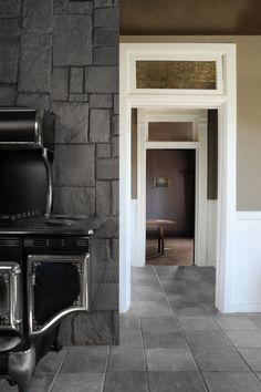 """Explains designer Lauren Lochry, """"A previous owner had installed the stove along with a refrigerator designed by the same manufacturer, Elmira Stoveworks. Elmira is very thorough in their replications."""" Adds Lauren, """"Each door, passageway, and window has custom millwork with matching ornamental framing motifs."""" The doors also feature framed transom windows that can be opened and closed with brass fixtures."""
