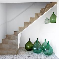 Demijohns clustered alongside a concrete stair in a vacation house on the border of Switzerland and Italy, discovered via Marie Claire Maison.