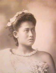 Woman in Wraparound Siapo Dress Andrew, Thomas  photographer  1890 - 1910 Portrait of an unknown woman with her hair up in a flower-petal headband, looking slightly to the (viewers') right. She is wearing a white shell/teeth lei and a wraparound over-one-shoulder siapo dress.