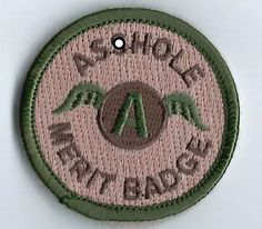Embroidered ASSHOLE MERIT BADGE MORALE patch. Velcro backing, Desert Scheme. 1.75 round