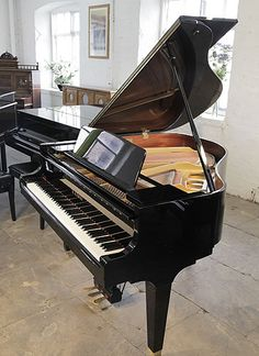 A Kawai GM10 baby grand piano for sale with a black case and square, tapered legs at Besbrode Pianos.