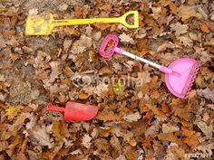 Schippen und Schaufeln in Gelb und Rot in einem Sandkasten mit Herbstlaub am Gut Wilhelmsdorf