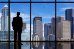 Silhouette of a Business Man looking out of high rise office window