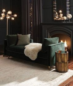 soft black living room with a dark green sofa, art deco lights and a working fireplace
