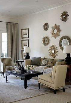 An arrangement of sunburst mirrors, interesting for its asymmetry. Decor by Suzanne Kasler for an Atlanta house. The row of prints balances the mirror arrangement.