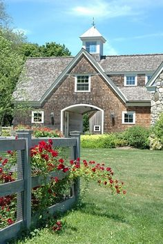 New England house with weathered cedar siding and cedar roof, extra wide arched door, white window trim, attached to original building of random shape stone, green hedge and other landscaping, spare weathered fence with rambling red roses