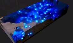 """In another stroke of breathtaking design and functionality, Alexandre Chapelin has expanded his La Table series to include a new model named """"Starry Sea."""" During the day, the table's blue resin of varying depths and hues resembles a slice of the Caribbean and, by night, it becomes illuminated with LED lights to reflect back a starry, spellbinding sky."""