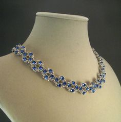 Handmade with Venus in Chains� unique Crystal Chain Maille Flower Pattern, this stunning necklace is elegantly woven with hundreds of genuine Sapphire Blue Swarovski Crystal Montees and silver toned jumprings.  Measuring at just over 16 inches in length, it perfectly frames the face and showcases the d�colletage.  Finished with a beautiful and easy to operate magnetic clasp, set with more lovely Swarovski crystals, this necklace is the perfect finishing touch for your next special occasion.