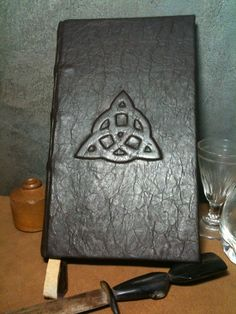 Make the triquetra of cardboard, back ridges of string, and cover with ripped, wrinkled pieces of brown paper bags; dye the color you wish...