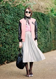 A pink top is paired with a monogrammed varsity jacket, scarf, metallic midi skirt, tights, heels, round sunglasses, and a Marc by Marc Jacobs bag