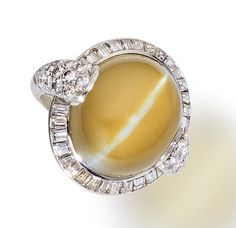 A chrysoberyl cat's eye and diamond ring  centering an oval cabochon chrysoberyl cat's eye within a surround of baguette-cut diamonds completed by shoulders of pavé-set round brilliant-cut diamonds;