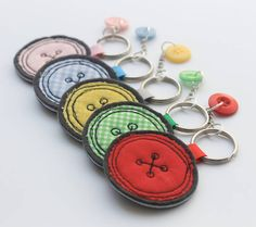 A pretty handmade keyring for that Button Lover out thereChoose from 5 different colours, red, green, pink, blue or yellow. A beautiful gift for any lover of Buttons or a sewing bee you know. Handmade using a freehand machine embroidery technique, and then finished with a seperate co-ordinating dangly button. This fabric button keyring has been handmade using pretty cottons, appliqued onto a hardwearing quality wool fabric. This also comes as a matching brooch. Comes with metal keyring. Due…