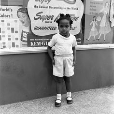 A little girl with shorts, shirt, and cornrows who looks at the artist with posters behind showing what real woman looks like and values. 1953, Queens, New York, NY