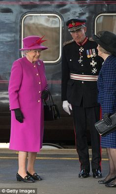 On duty: The Queen, who was wearing a cheerful purple ensemble, steps off the train at Ply...