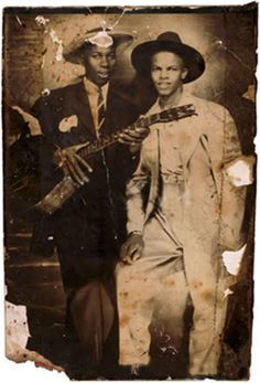 "Robert Johnson (with Johnny Shines ?)  There are two ""known"" photos of Robert Johnson.     The first is the Studio Portrait taken by Hooks Brothers Photography Studio in Memphis, Tennessee and kept by Johnson's half-sister Carrie Spencer in her Bible. The dark three-piece suit Johnson wears really belonged to his nephew Louis, Carrie's son. Louis was about to go into the Navy and was having his picture taken in his uniform. He asked his favorite uncle Robert to pose with him. Acco"