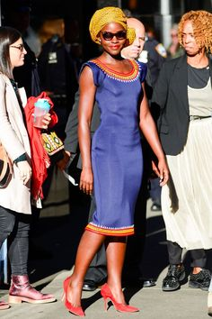Lupita Nyong'o in a blue boatneck dress with a red and yellow trim, red suede pumps, yellow head wrap and oversized sunglasses while out in New York. Celebrity Outfits, Celebrity Style, Zendaya, Best Street Style, Boat Neck Dress, African Design, Red Carpet Dresses, Red Carpet Fashion, African Fashion