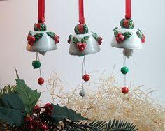 Campanelle piccole in ceramica con decorazioni natalizie. Fatto di terra bianca e dipinto a mano.Christmas bells